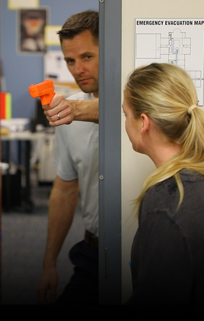 A man with a fake orange gun is hiding behind a door frame, simulating active shooter training